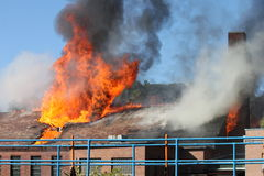 Factory Fire. Factory up in blazing flames with billowing smoke royalty free stock image