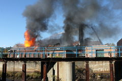Factory fire. Old factory up in blazing flameswith black smoke Stock Photo