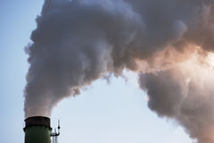 Factory flue and water steam. On a blue sky background stock image