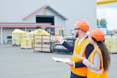Factory Foreman Giving Instruction to Worker. Side view portrait of successful bearded businessman wearing hardhat and holding clipboard talking to female royalty free stock photo