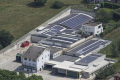 A factory full of solar panels with a green grass and trees around it. Composition stock image