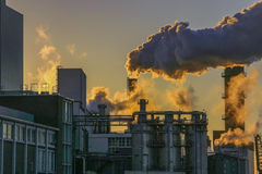 Factory fumes. Dangerous fumes coming from factory pipes against beautiful sunset royalty free stock photography