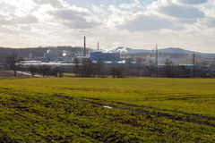 Factory, green field and cloudy sky Royalty Free Stock Photos