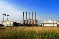 Factory and green meadow Stock Photos