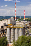 Factory with grungy cisterns. Big factory with several chimneys and cistern on a blue sky and beautiful landscape in the background Royalty Free Stock Image