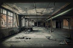 Factory hall ruin. Desolate hall of a factory ruin. Light is shining through the broken windows Stock Photography