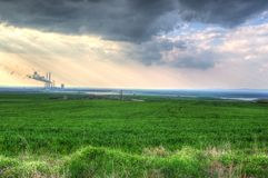 Landscape with a factory pollutes the air and dark stormy clouds Royalty Free Stock Photo