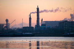 Factory in the Late Afternoon. With River in the Foreground Royalty Free Stock Photography