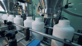 Factory machines filling plastic bottles, automatic process.