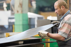 Factory man worker holding metal sheet in workshop royalty free stock photography