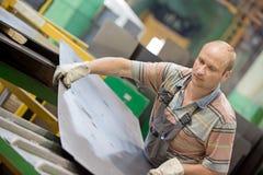 Factory man worker moving metal sheet in workshop Royalty Free Stock Image