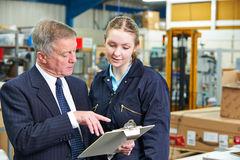 Factory Manager And Apprentice Engineer Looking At Clipboard. Factory Manager And Apprentice Engineer Look At Clipboard Royalty Free Stock Image