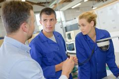 Factory manager and engineering apprentices discussing component royalty free stock image