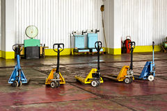 Factory manual forklifts. Group of manual forklifts parked in factory warehouse Stock Photography