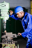 Factory mechanic. African american factory mechanic operating a drilling machine stock image