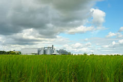 Factory in the middle of a green farmland on a cloudy day Royalty Free Stock Photography