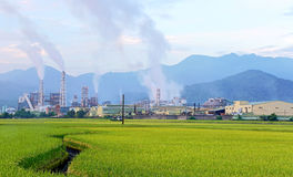 Factory in the middle of a green farmland on a cloudy day Stock Photo