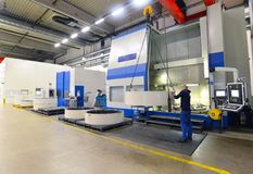 Factory of modern mechanical engineering - production of gearbox. Es for wind turbines - worker at cnc milling machine royalty free stock photos