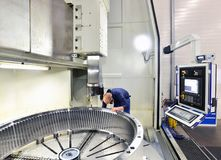 Factory of modern mechanical engineering - production of gearbox. Es for wind turbines - worker at cnc milling machine stock images