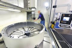 Factory of modern mechanical engineering - production of gearbox. Es for wind turbines - worker at cnc milling machine stock photos