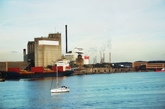 Factory near sea in Aalborg, small yacht on water passing by Stock Images