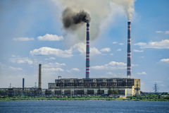 Factory next to river with air pollution Stock Photography