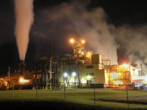 Factory at Night. The smoke and steam rising into the night sky combined with the �eyes� peering through the fog seem to give this shot a surreal feeling Royalty Free Stock Photo