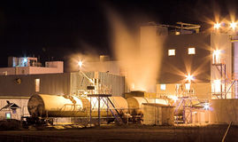 Factory At Night. Factory at night with steam Stock Photo