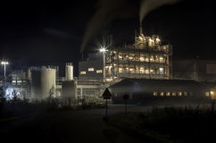 Factory at night. A factory building at night with smoke from the chimney royalty free stock images