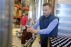 Factory operative packing bottles from end production line Stock Image