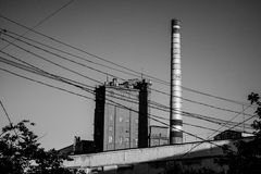 Factory photo with steam tube in the sunset light. Black and white photo. Factory photo with steam tube in sunset light. Black and white photo royalty free stock image