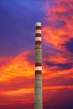 Factory pipe. Old factory pipe against red, dark blue clouds Stock Photo
