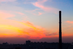 Factory pipe in the city at a beautiful sunset Royalty Free Stock Photo
