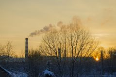 The factory pipe smokes against the background of a red sunset. Industrial landscape Stock Photo