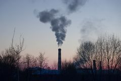 The factory pipe smokes against the background of a red sunset. Industrial landscape Stock Image