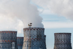 Factory pipes or Cooling towers of nuclear power plant with steam. Environmental. Pollution concept stock image