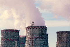 Factory pipes or Cooling towers of nuclear power plant with steam. Environmental. Pollution concept royalty free stock photos