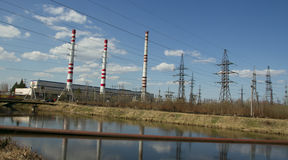 Factory pipes and high voltage power lines. Against the blue sky and the spring forest Stock Images