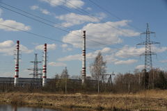 Factory pipes and high voltage power lines. Against the blue sky and the spring forest Stock Photography