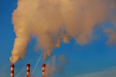 Factory pipes smoke in the blue sky. And pollute environment Royalty Free Stock Photo