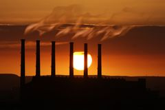 Factory Pollution. Smoking factory chimneys at sunset adding to global warming stock images