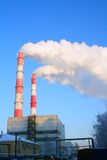 Factory pollution. Two large factory chimneys emitting clouds of white smoke, blue sky background Royalty Free Stock Photography