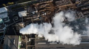 Factory on processing of a tree. The smoke from the chimneys.  royalty free stock photography