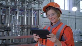 Factory profession, female engineer in hard hat uses tablet computer and makes photos for scanning equipment in plant