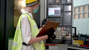 Factory professional manager woman inspects on panel heavy machine with report paper and walking around machine. Quality assurance