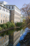 Factory reflection along the river. An old factory building, lining a small river, with its reflection visible in the still water Royalty Free Stock Image