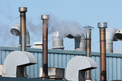 Factory Roof. Detail of factory roof with ventilation ductwork and steam vapour stock image