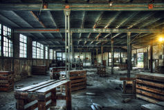 Factory Ruin. HDR - old abandoned factory interior with wooden tables and boxes stock photo