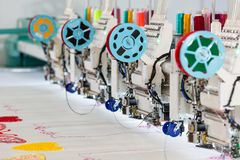 Factory sewing machine makes color pattern closeup. Textile fabric, nobody. Sew manufacturing, needlework technology Stock Photos