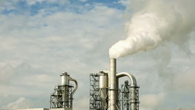 Factory smoke stack and pipes puff into air stock footage